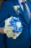 The groom in a suit or Young girl-bride or bridesmaid is holding a wedding bouquet. The groom in a suit or Bridesmaid is holding a wedding bouquet before church Stock Photos