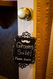 Groom Suite Please Knock Sign. Sign reads groom's suite please knock hung on the door handle royalty free stock images