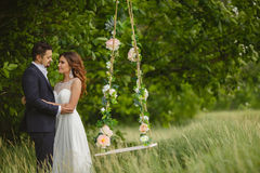 Groom swings the bride on a swing in outdoor park Stock Images