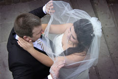 Groom takes down the veil. Loving newlyweds kiss passionately. View downwards Stock Photos