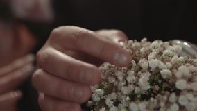 Groom takes an engagement ring lying in flowers, during a wedding ceremony, close-up, slow motion. Groom takes engagement ring lying in flowers, during wedding stock video footage