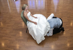 Groom taking off garter. A groom under brides dress to take off garter during reception Royalty Free Stock Photo