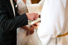 Groom taking rings in wedding ceremony. Couple having their wedding ceremony in church in front of a catholic priest, groom taking the ring to give it to the Stock Image