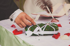 Groom taking wedding ring from the pillow Stock Photography