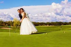 Groom teaching bride to play golf royalty free stock photos