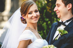 Groom looks with love at shiny pretty bride stock images