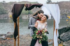 Groom tenderly embracing her beautiful bride by behind. Autumn wedding ceremony in rustic style outdoors. Happy Stock Photography