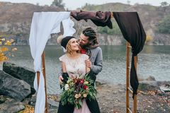 Groom tenderly embracing her beautiful bride by behind. Autumn wedding ceremony in rustic style outdoors. Happy Royalty Free Stock Photography