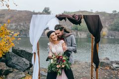 Groom tenderly embracing her beautiful bride by behind. Autumn wedding ceremony in rustic style outdoors. Happy Stock Image