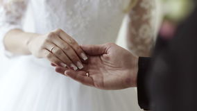 Groom tenderly holds the hand of the bride stock footage
