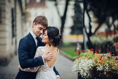 Elegant bride with groom walking near old catholic cathedral. Groom tenderly hugging asian bride in white dress stock images