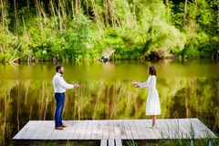 The groom throwing bridal bouquet to the bride near the lake Royalty Free Stock Image