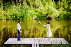 The groom throwing bridal bouquet to the bride near the lake Royalty Free Stock Photos