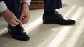 Groom tie shoelaces on black shoes at home before visiting bride stock footage