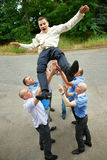 Groom tossed  by a group of groomsmen Stock Image