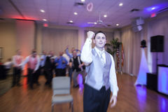Groom tossing garter. A groom throwing brides garter during reception Stock Images