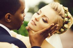 Groom touches face of bride. Loving groom african American men gently touches face of beautiful bride blond women with elegant hairstyle and wreath outdoors on stock photography