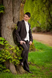Groom at tree Royalty Free Stock Photo