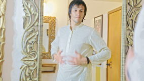 Groom Tries on Traditional Indian Dress before Mirror stock video