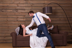 Groom trying to choke bride in white dress. And veil, he shouting at her. Newlyweds complex relationship stock images