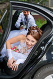 Groom trying to drag the bride out of the car Stock Image