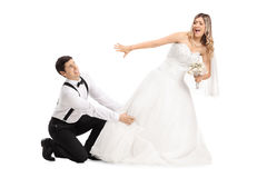 Groom trying to stop his bide from running away Stock Image