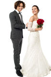 Groom tucking brides dress Stock Photography