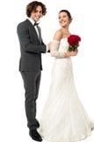 Groom tucking brides dress Stock Photography