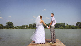 Groom turns back. Young happy newlyweds walking and posing on a riverside Stock Images