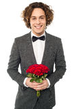 Groom in tuxedo posing with a bouquet Royalty Free Stock Photo