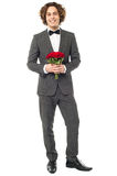 Groom in tuxedo posing with a bouquet Royalty Free Stock Photos
