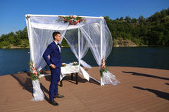 The groom under a canopy. Groom before wedding ceremonial act in front of the canopy raft expected arrival of their chosen royalty free stock photos