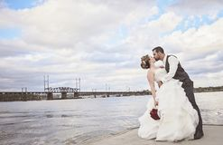 Wedding kiss. A groom in uniform kissing his bride on a pier by the water Stock Photos