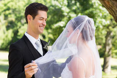 Groom unveiling his bride in garden Royalty Free Stock Photography