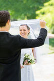 Groom unveiling his bride in park Stock Image