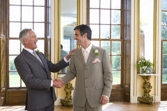 Groom and usher shaking hands, smiling at each other, side view Stock Photo