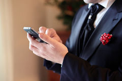 Groom using mobile phone Royalty Free Stock Image