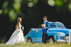 Groom Waiting For Bride at Cabriolet. Groom with bouquet waiting for bride at blue cabriolet Royalty Free Stock Photos