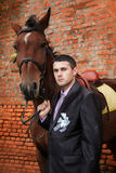 Groom  during walk  against a brown horse and old brick wall Stock Images