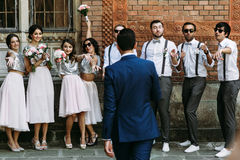 Groom is walking to the groomsmen and bridesmaids Royalty Free Stock Image