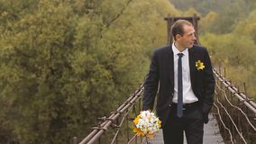Groom Walking Through the Wooden Bridge in the Mountains. Slow motion stock video footage