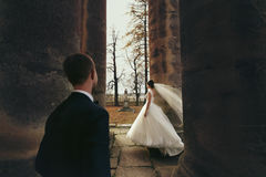 Groom watches a bride while wind blows her veil around the pilla Royalty Free Stock Images