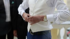 Groom wearing buttoning white jacket stock footage