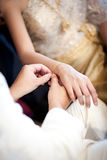 Groom wearing gold bracelet for his bride in wedding ceremony Royalty Free Stock Photo