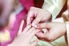 Groom wearing ring on bride's finger Stock Photos