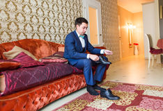 Groom is wearing shoes indoors. Male portrait of handsome guy. Beautiful model boy in colorful wedding clothes. Royalty Free Stock Photography