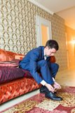 Groom is wearing shoes indoors. Male portrait of handsome guy. Beautiful model boy in colorful wedding clothes. Stock Images