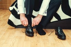 Groom wearing shoes on wedding day, tying the laces, preparing Stock Images