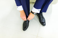 Groom wearing shoes on wedding day, tying the laces and preparing. Business man dressing up with shoes. Stock Photo