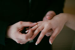 Groom wearing the Wedding Ring on bride. He Put the Ring on Her. Royalty Free Stock Photo